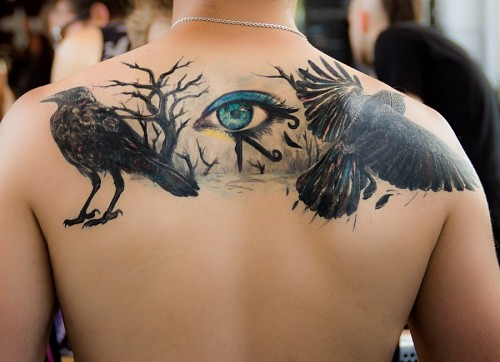 Horus eye tattoo on men's back