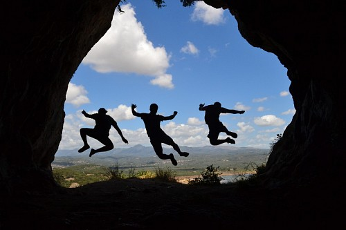 Silhouettes of friends taking a leap