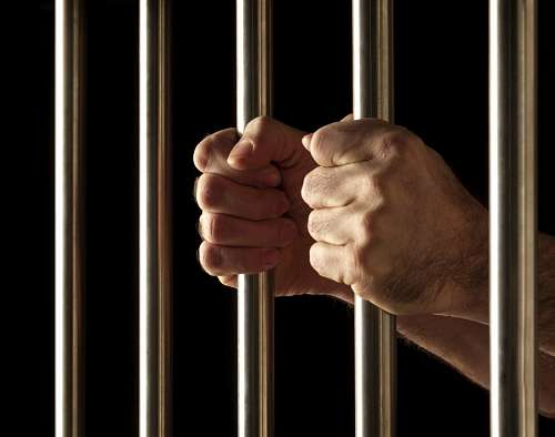free images  Man's hands taking prison bars