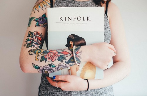 Girl with arms tattooed holding book