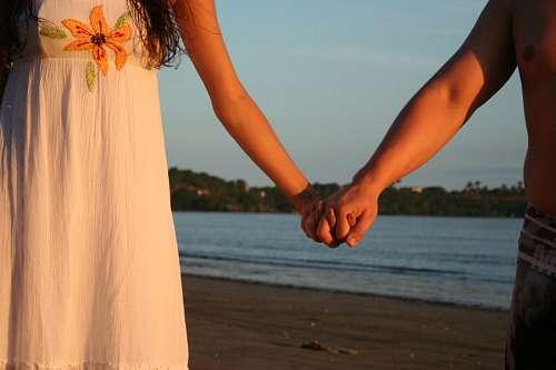 Pareja tomados de la mano frente al mar