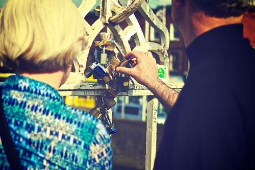 free images  Bride and groom closing a lock on the bridge of lovers