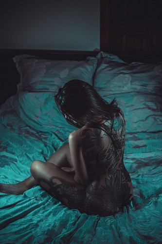 Nude woman with tattoos lying on the bed