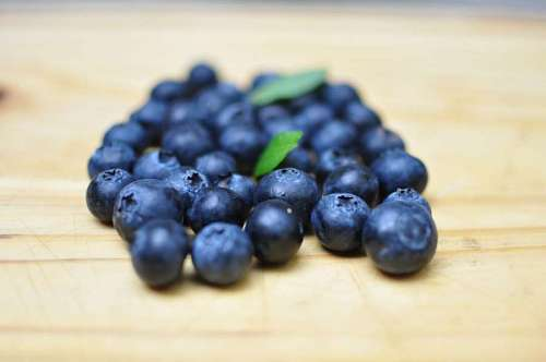 Selective focus of blueberries over wood background