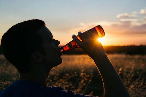 free images  Man drinking a beer at sunset