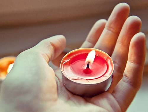 Hand holding a light candle