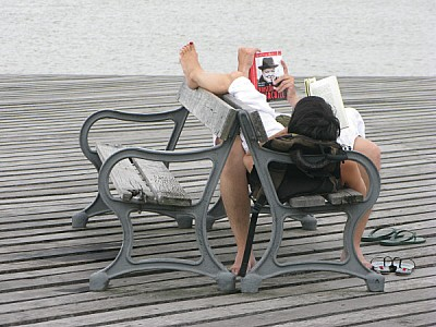 Couple reading on a pier in Colonia, Uruguay